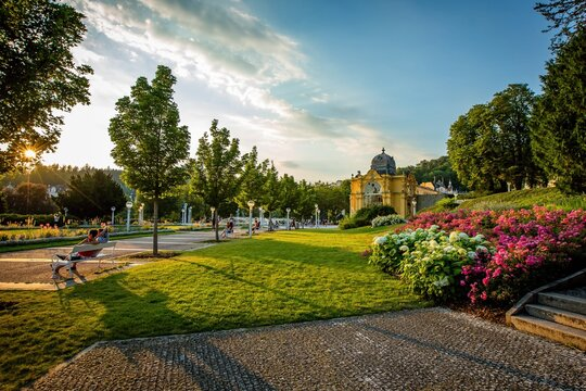 Marianske Lazne / Czech Republic - August 8 2020: View of the Maxim Gorky colonnade and singing water fountain. Colorful flowers, green lawn. Summer sunset in famous spa city with blue sky and clouds.