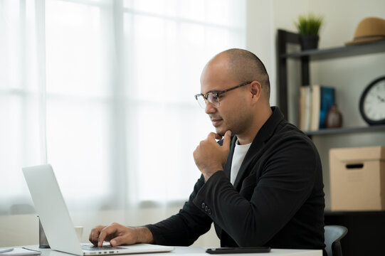 A middle-aged man around the age of 35. Working at home Work through the laptop by meeting video conference. He was wearing a black suit and glasses. Smiling asian businessman work from home.