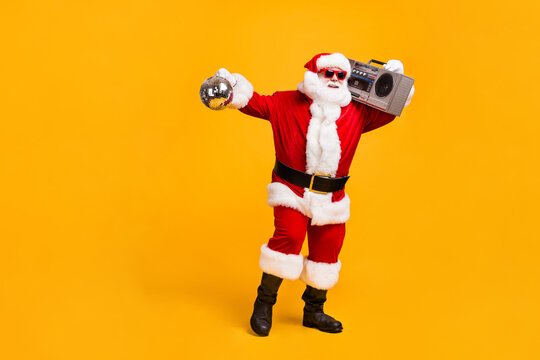 Full length photo of funky santa claus with grey beard hold boom box disco ball x-mas christmas jolly holly eve time party wear headwear red cap isolated yellow color background