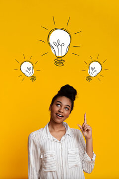Great idea. Pretty African American woman with light bulbs over her head pointing up on yellow background, collage
