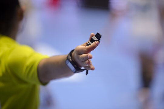 Shallow depth of field with handball referee hand holding a whistle