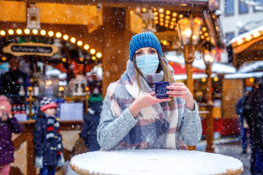 Woman with medical mask drinking hot punch, mulled wine on German Christmas market. People with masks as protection against corona virus. Covid pandemic time in Europe and in the world.