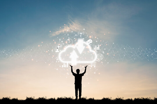 Cloud computing and technology transformation concept , silhouette of businessman standing and two rise hand up for holding virtual cloud computing and icons.
