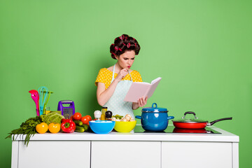 Photo of minded ponder girl look cook book decide what fresh organic veggie dish prepare touch chin hand wear hair rollers yellow dotted t-shirt isolated over green color background