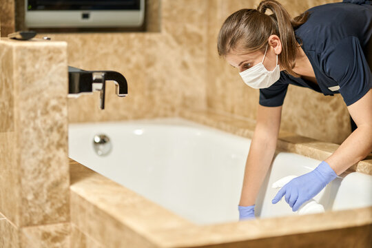 Chambermaid in mask leaning into the bathroom and washing in