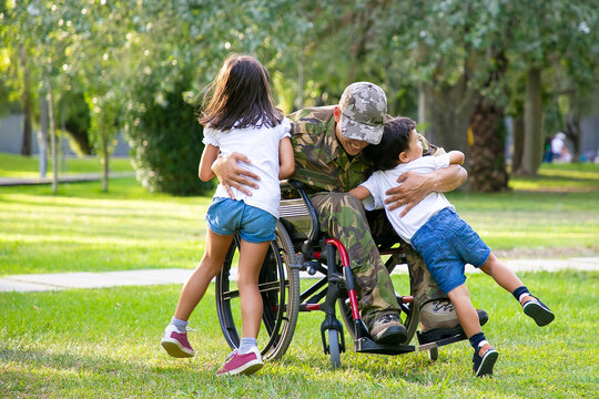 Happy disabled military man in wheelchair returning home and hugging kids. Veteran of war or family reunion concept