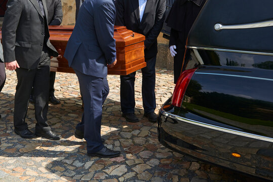 Group of survivors carries a coffin out of the church after a funeral mass