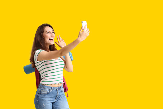 Female tourist taking selfie on color background