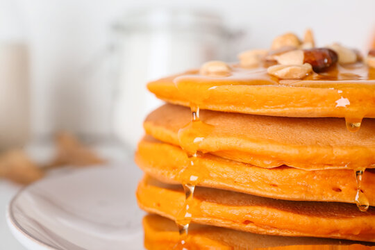 Tasty pumpkin pancakes with honey on plate, closeup