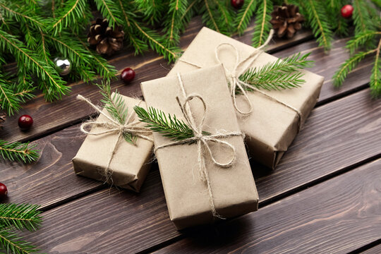 Christmas gift boxes with fir tree branches on wooden background