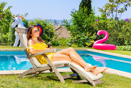 Beautiful teenage girl sit on the chaise longue near pool during summer vacation and drinking cold soda