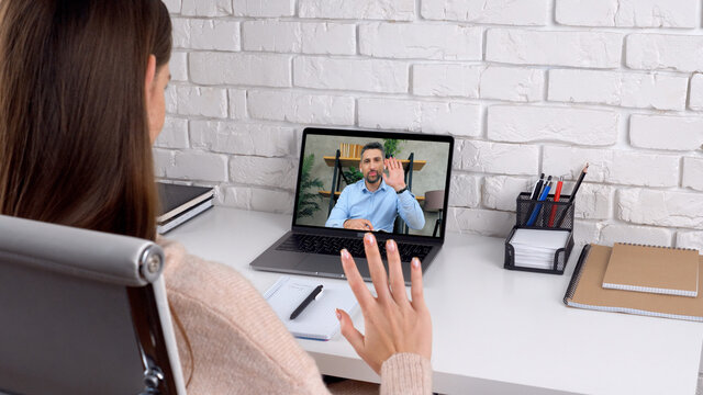 Man tutor in computer screen greets talk teaches by remote webcam, distance education. Over the shoulder woman student studying at home office online by conference video call laptop