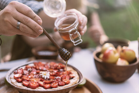 Hand pouring honey on strawberry pie in the garden