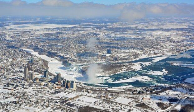 Aerial view across Niagara Falls Ontario, towards the falls and Niagara Falls New York, snow covered ground and ice on the Niagara river