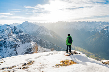 Tourist with a backpack and mountain panorama. Climber in a green jacket climbs a mountain against a blue sky. Hiker with backpack standing on top of a mountain and enjoying view. Adventure concept