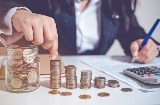 Closeup image businesswoman holding coins putting to stacking coins bank and calculating. concept saving money wealth for finance accounting.
