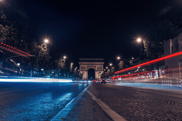 View of vehicles driving on street leading towards Porte Saint Martin at night Fotomurales