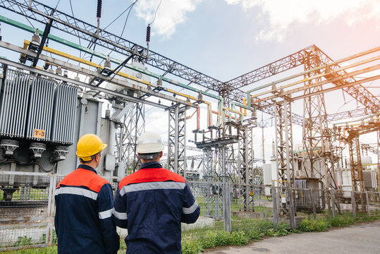 Two specialist electrical substation engineers inspect modern high-voltage equipment during sunset. Energy. Industry