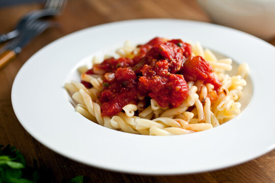 Pasta with pungent tomato sauce with capers and vinegar served on plate