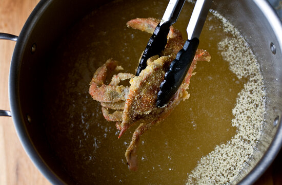 Overhead view of softshell crab with cornmeal coating frying in oil