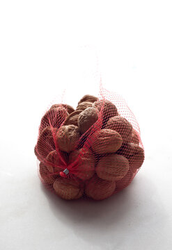 Close up of walnuts in mesh bag on table