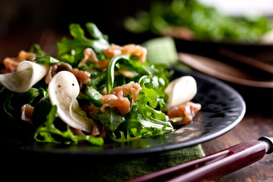 Close up of turnip salad with arugula and prosciutto served on plate