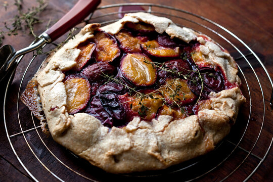 Close up of rustic plum crostata with lemon thyme on cooling rack
