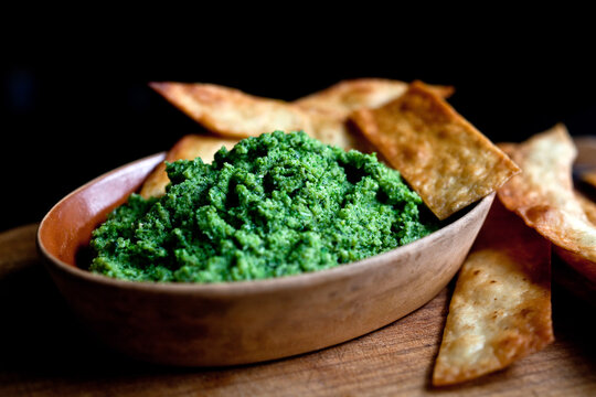 Close up of broccoli pesto served with tortilla chips on table