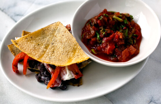 Close up of black bean and goat cheese quesadilla served with salsa