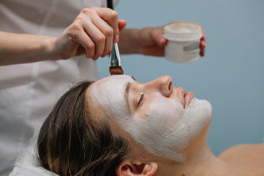 Unrecognizable beautician apply mask