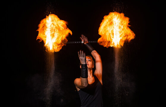 Sensual fire actress manipulate flaming baton in night darkness outdoors, theatre