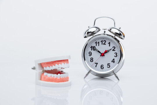 Jaw model and alarm clock on a table. Time to visit a dentist.