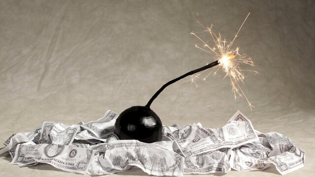 A bomb with a lit fuse sits on a pile of 100 dollar bills.