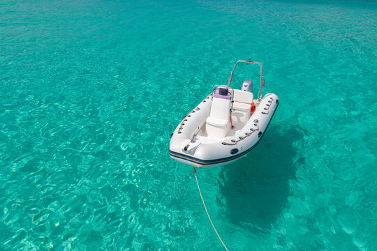 water craft sitting in clear blue ocean waters in the middle of summer