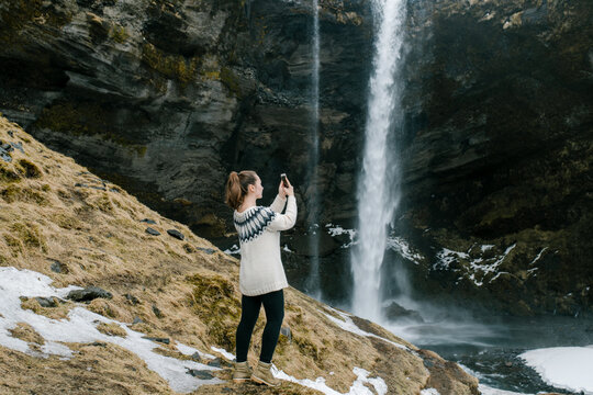 A girl traveler taking a photo of a beautiful waterfall on her smartphone