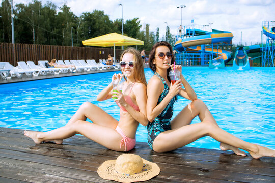Sexy tanned girls relaxing near the city pool and drinking tropical cocktails. Beautiful  smilled girls in sunglasses enjoying the summer day and vacation.