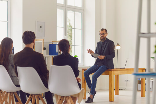Young businessman speaker or company owner making presentation for office workers
