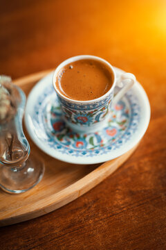 Traditional sparkling turkish coffee served with porcelain cup and flower.