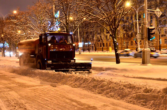 Clearing the streets of snow after a snowfall. Front view of snowplow service truck and gritter spreading salt on the road surface to prevent icing in stormy snow winter day.