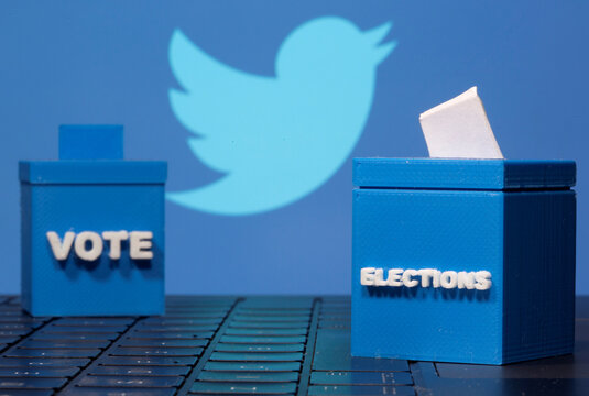 3D-printed ballot boxes are seen in front of a displayed Twitter logo