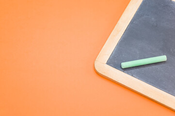 Top view of the blackboard with chalk on the orange surface