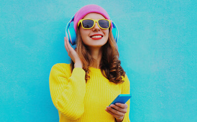 Portrait of modern young woman in wireless headphones listening to music with phone wearing yellow knitted sweater and pink hat on blue background