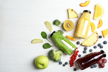 Bottles of delicious juices and fresh fruits on white wooden table, flat lay. Space for text