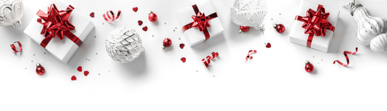 Merry Christmas card made of gift boxes, red and silver decoration, sparkles and confetti on white background. Xmas and New Year holiday, bokeh, light. Flat lay, top view, frame