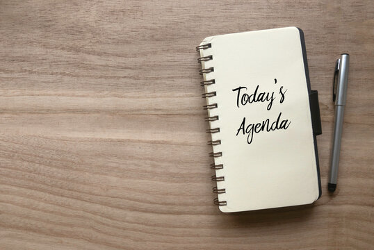 Top view of pen and notebook written with Today's Agenda on wooden background with copy space.