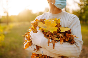 Cleaning of fallen yellow leaves in the city of quarantine. Men in protective medical mask and  gloves cleans autumn leaves in the park.