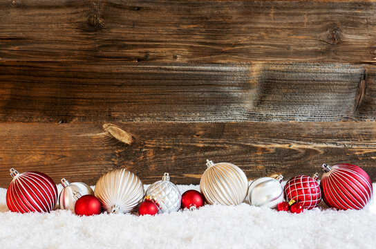 Copy Space For Advertisement On Rustic Brown Wooden Backgroud. Red And White Festive Christmas Ball Ornament On Snow.