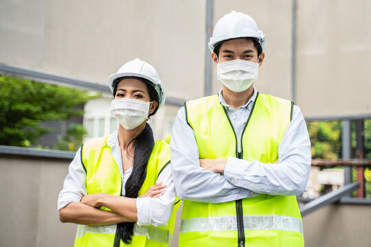 Asian young engineer man and woman wear face mask to prevent COVID-19.