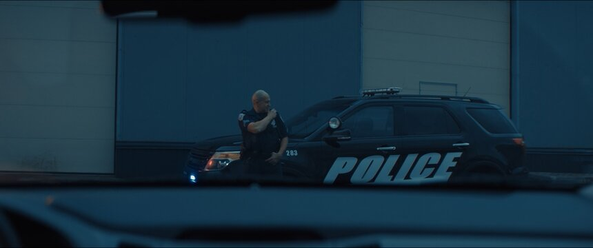 Caucasian male police officer standing guard in the street near police car with flashing lights, talking on CB radio