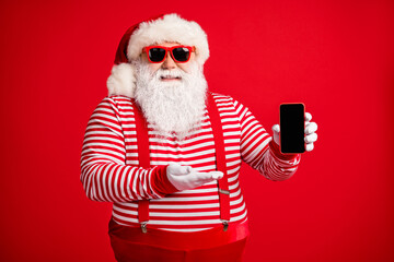 Portrait of his he nice handsome cheerful bearded fat Santa holding in hand demonstrating novelty gift present surprise gadget isolated on bright vivid shine vibrant red color background
